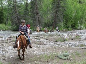 Paarden en ruiters steken rivier over